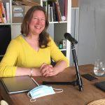 Zu sehen: Autorin Maren Martschenko mit langen Haaren und einem gelben Pullover an einem Holztisch vor einem Mikrofon.